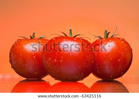Three juicy tomatoes on an orange background - stock photo