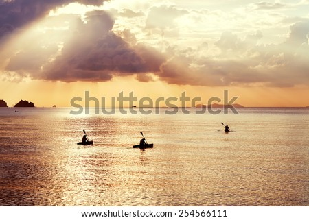 three kayak float at sunset - stock photo