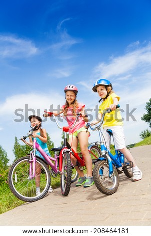 Three kid girls holding bicycles outdoors