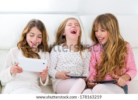 three kid sister friends girls group playing together with tablet pc on white sofa - stock photo