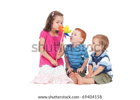 Three kids blowing toy windmill.  Isolated on white. - stock photo