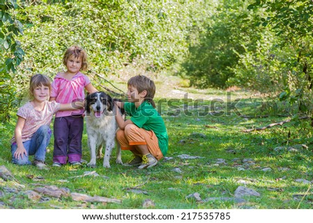 three kids - boy and girls - with dog outdoors - stock photo