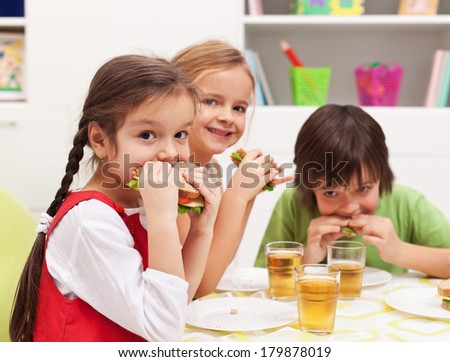 Three kids chomping on healthy sandwiches with cheese and vegetables - stock photo