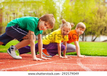 Three kids close-up in uniforms ready to run - stock photo