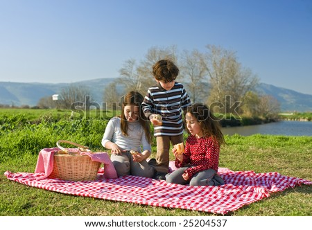 Three kids eating sandwiches at a picnic - stock photo