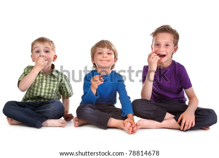 three kids eating sweets on white background - stock photo