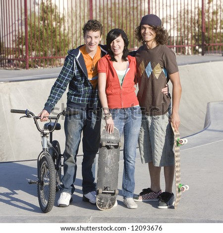 Three kids hang out at the skatepark