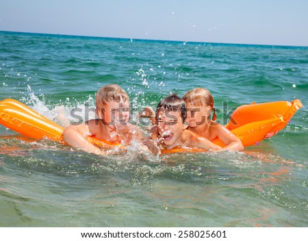 Three kids having fun floating on a inflatable mattress in the sea - stock photo