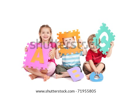 Three kids having fun learning with alphabet ABC letters. Isolated on white.