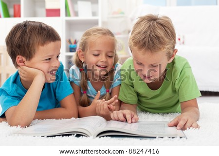 Three kids having fun reading a book laying on the floor - stock photo