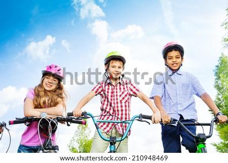 Three kids in helmets hold bike handle-bars - stock photo