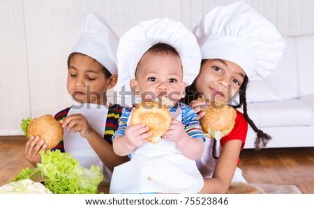 Three kids in white aprons and hats eating sandwiches - stock photo