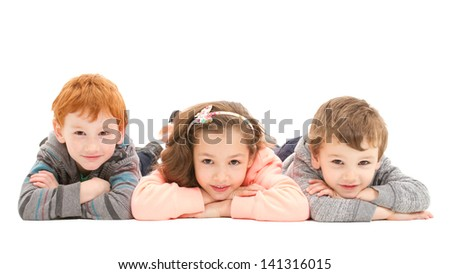 Three kids laying on floor.  Isolated on white. - stock photo