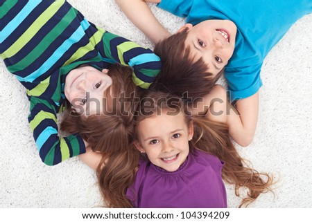 Three kids laying on the floor together - childhood friendship - stock photo
