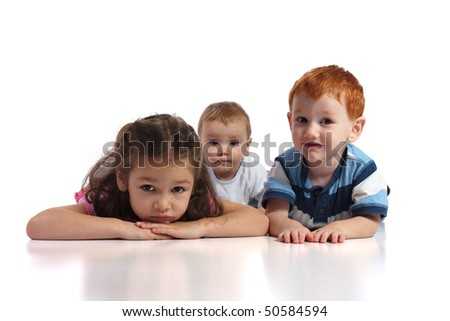 Three kids lying on floor facing camera. Isolated white background, foreground reflection. - stock photo