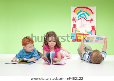 Three kids lying on floor reading books. On white and green. - stock photo