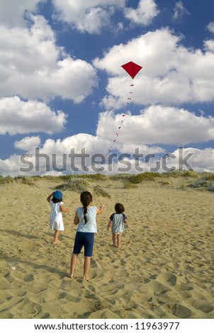 three kids on a beach playing with a red kite