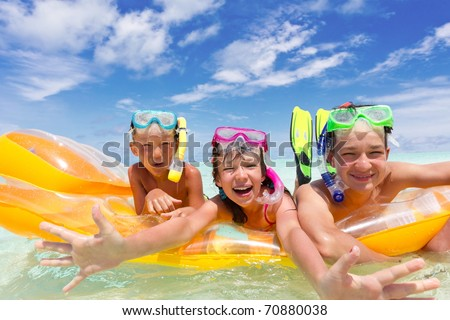 Three kids on a raft. - stock photo