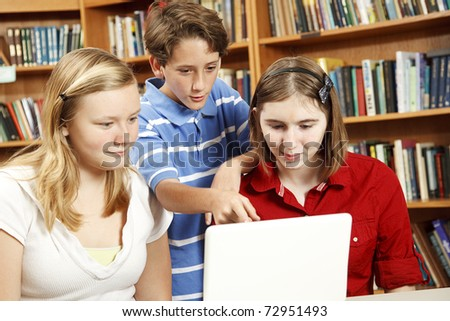 Three kids on the computer in the school library. - stock photo