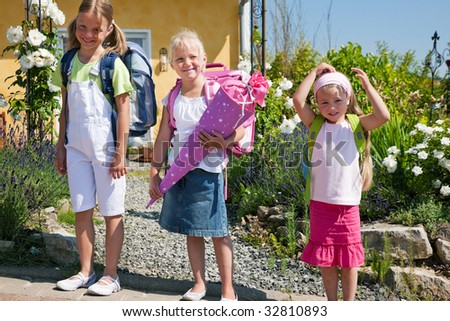 Three kids on the way to school, one with a traditional cone filled with sweet stuff - stock photo