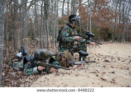 Three kids outside playing paintball in winter. - stock photo