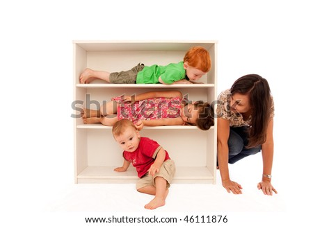 Three kids playing hide and seek on bookshelf with mum looking - stock photo