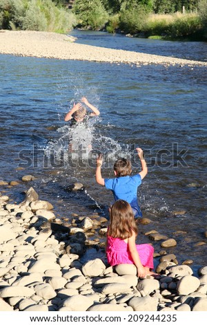 Three kids playing in shallow water on pebble beach