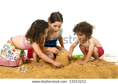 three kids playing in the sand isolated on white - stock photo