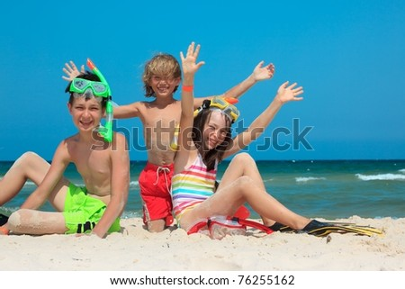 Three kids playing in the sand on the beach. - stock photo