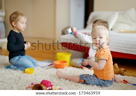 Three kids playing together at home - stock photo