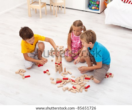 Three kids playing with wooden blocks in their room - top view - stock photo
