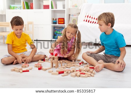Three kids playing with wooden blocks sitting on the floor