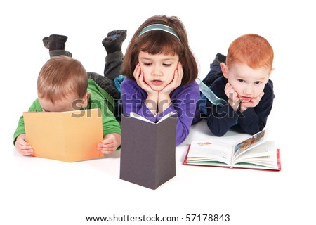 Three kids reading books lying on floor - stock photo