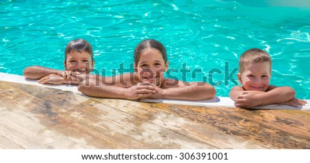 Three kids relaxing on swimming pool, summer concept - stock photo