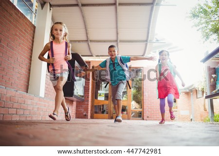 Three kids running in the playground on a sunny day - stock photo