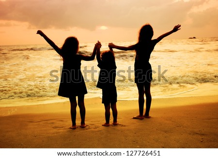three kids silhouettes standing on beach at sunset - stock photo