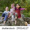 three kids siting on a rock singing outdoors - stock photo