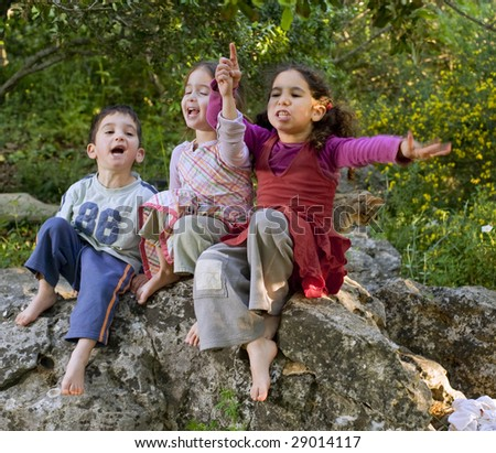 three kids siting on a rock singing outdoors