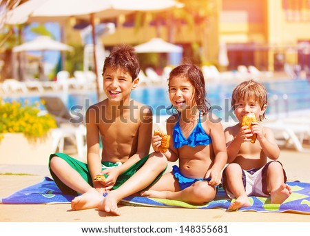 Three kids sitting down and eating croissant near pool, picnic outdoors, beach resort, summer vacation, happy childhood concept - stock photo