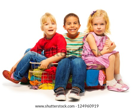 three kids sitting in the clothes basket - black boy and two blond girls - stock photo