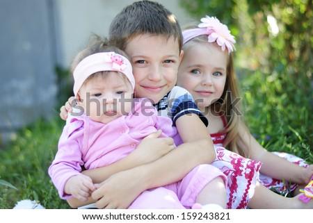 Three kids sitting near flowers - stock photo