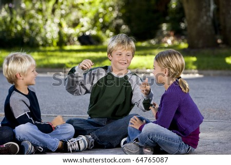 Three kids sitting on driveway playing, smiling and talking.  Ages 7 to 9 - stock photo