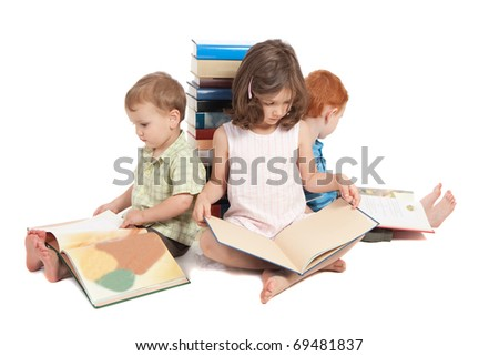 Three kids sitting on floor reading books and leaning against stack. Isolated on white