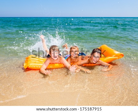 Three kids splashing water on a beach - stock photo