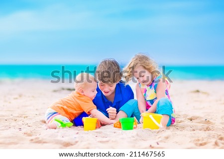 Three kids, teen age boy, little toddler girl and a funny baby playing together digging in sand with colorful toys, spade and buckets, relaxing on a sunny tropical beach during family summer vacation - stock photo