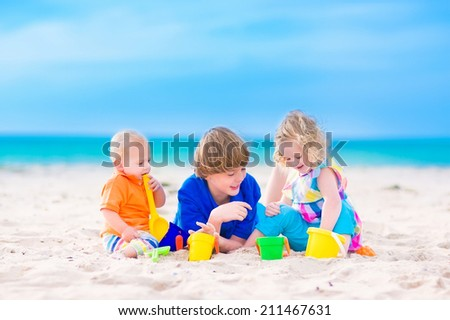Three kids, teen age boy, little toddler girl and a funny baby playing together digging in sand with colorful toys, spade and buckets, relaxing on a sunny tropical beach during family summer vacation