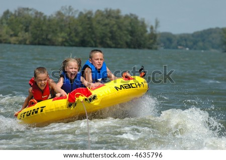 three kids tubing behind a boat - stock photo