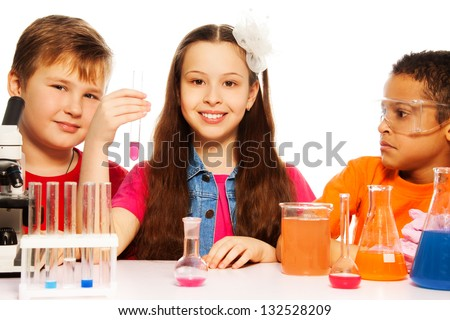Three kids, two boys black and white and brunet girl with microscope, test tubes and flasks conducting experiments, isolated on white - stock photo