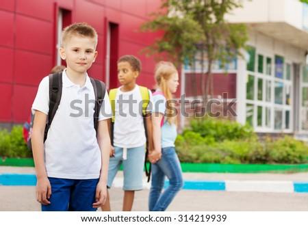 Three kids with rucksacks near school facade - stock photo