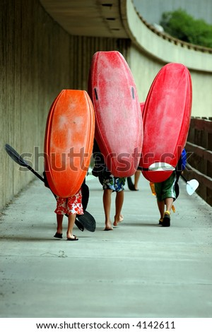 three kids wtih kayaks on heads walking on Glenwood Canyon bikepath - stock photo